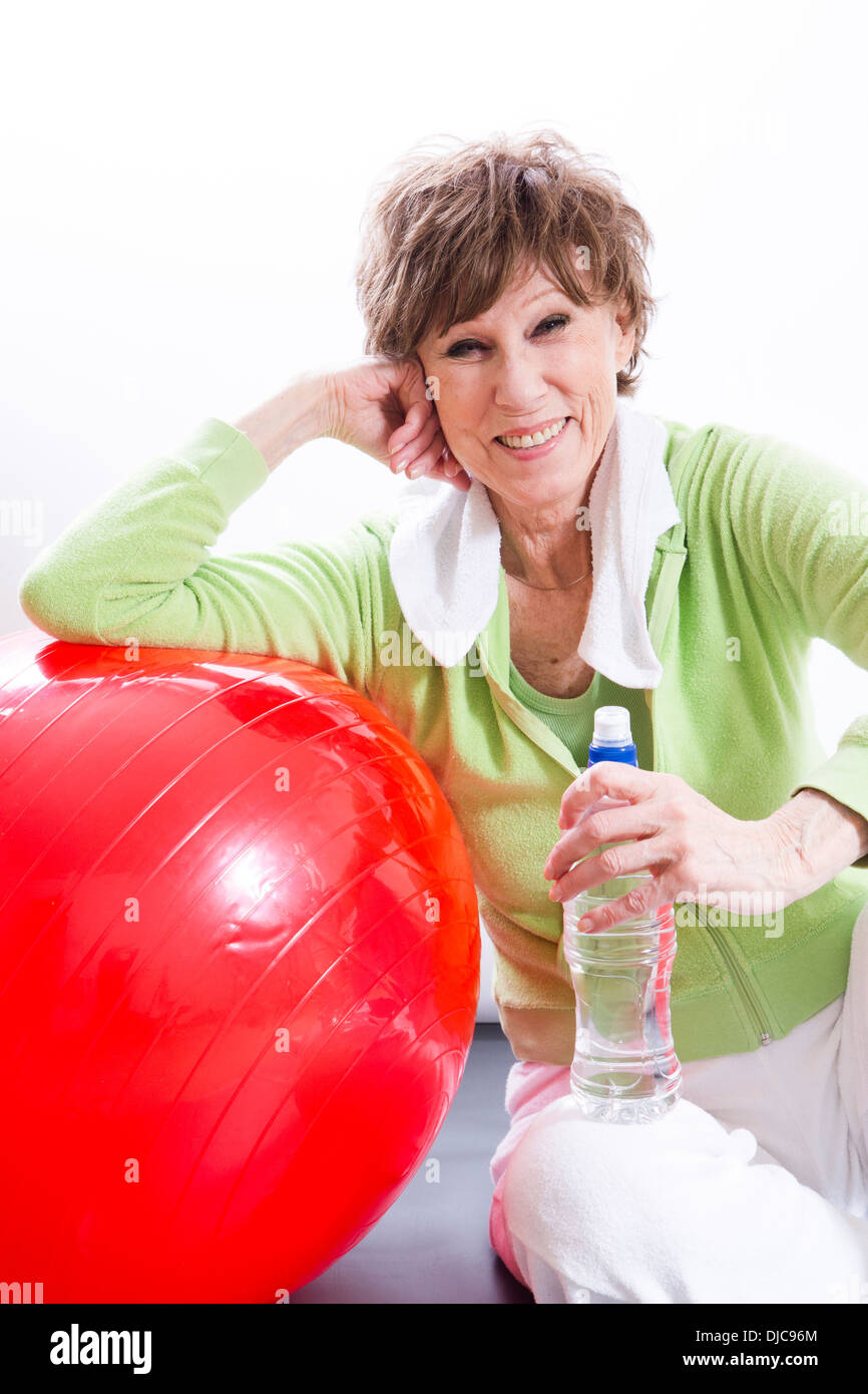 Mature woman leaning against exercise ball with bottled water - Stock Image