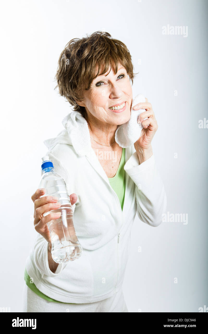Mature woman dabbing sweat and holding water bottle - Stock Image