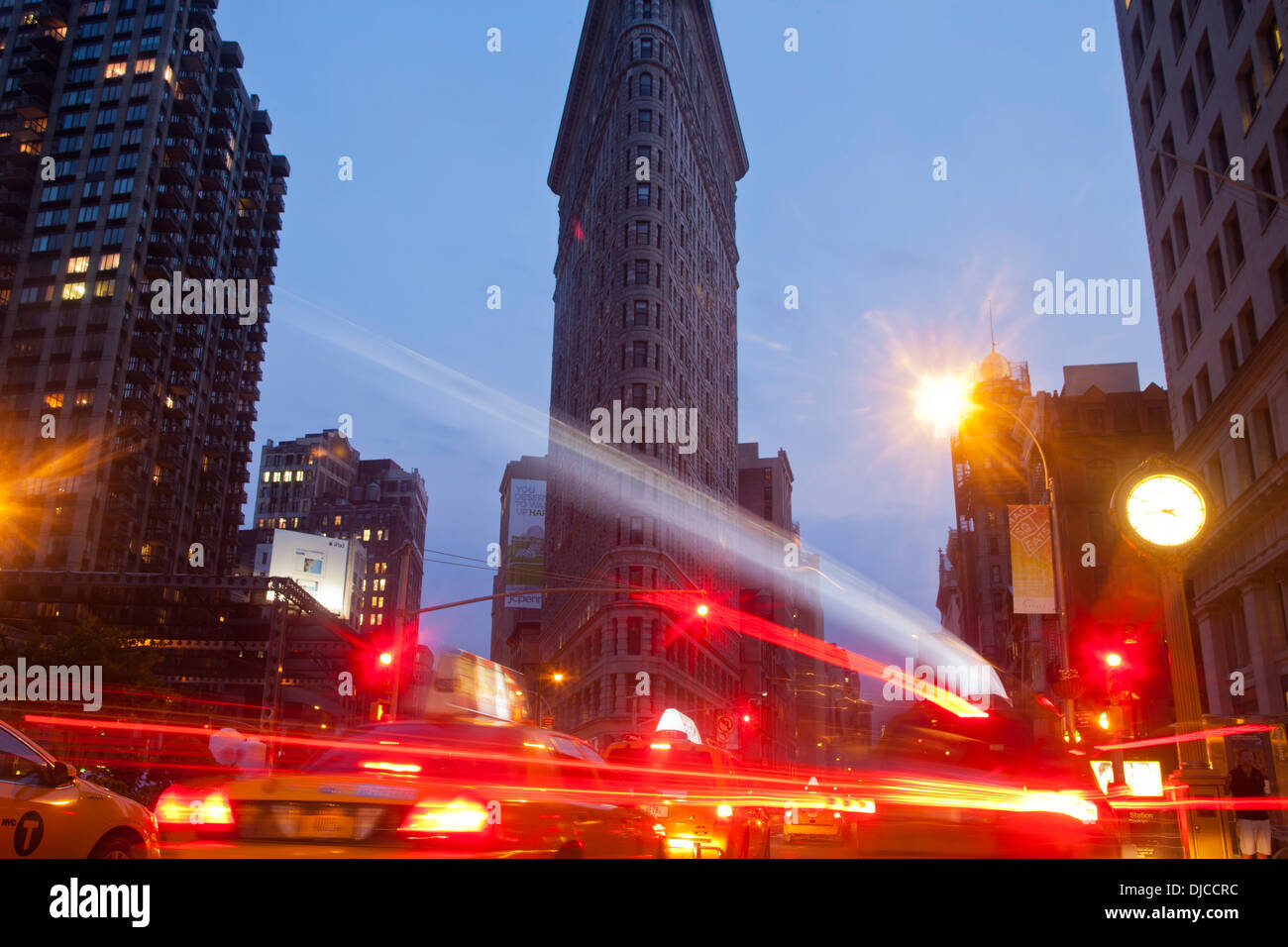 Traffic streaks down 5th Avenue next to the Flat Iron Building at dusk, New York City, USA - Stock Image