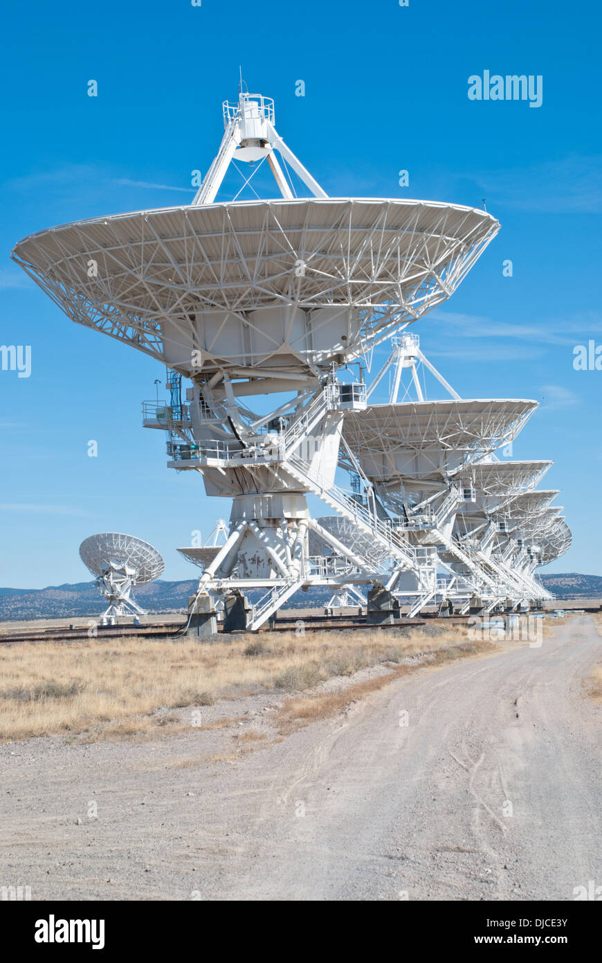 The massive radio telescopes at the Very Large Array  stand in stark contrast to the blue New Mexico sky. Stock Photo