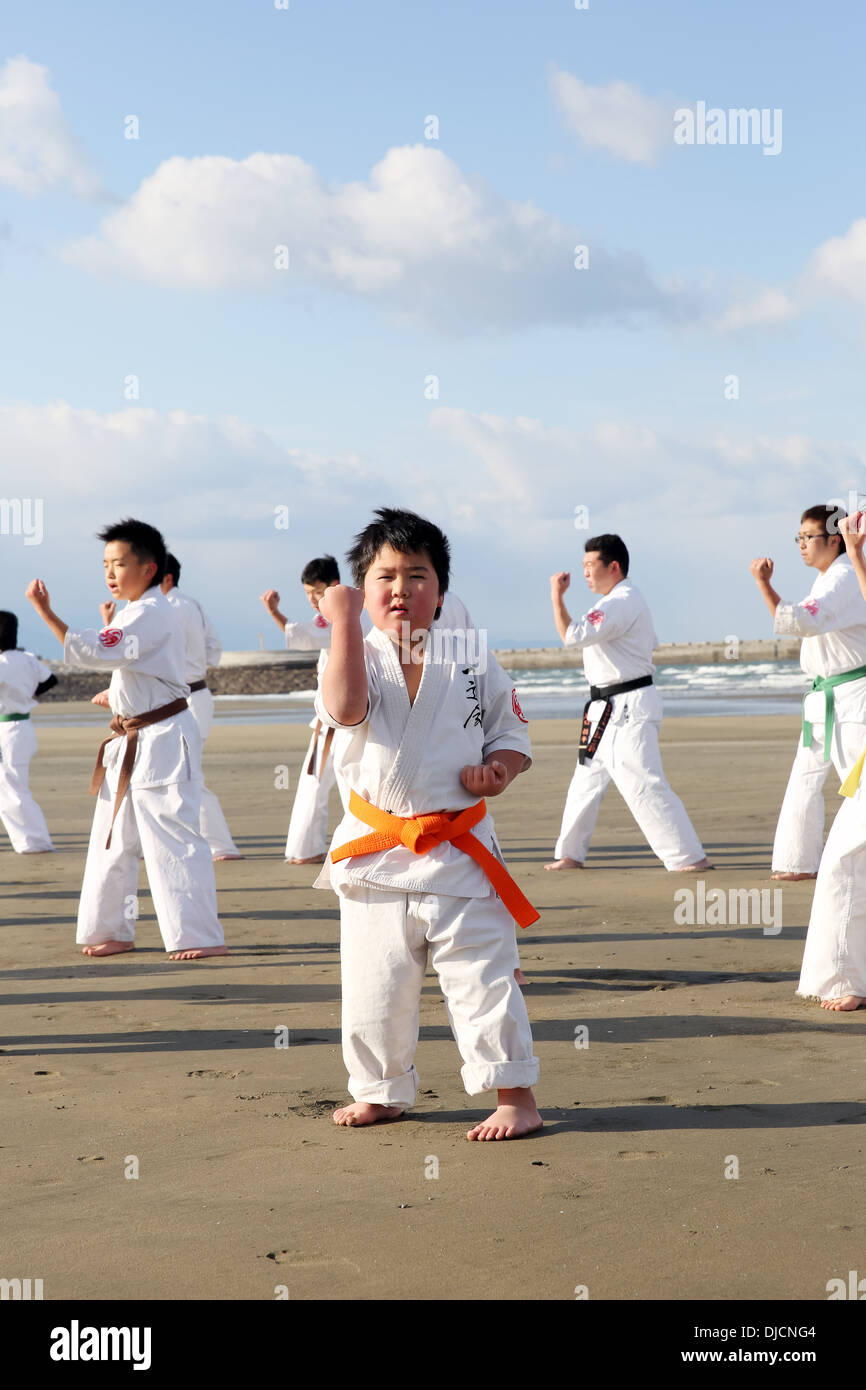 Training of Karate boy at the beach of midwinter, Japan - Stock Image