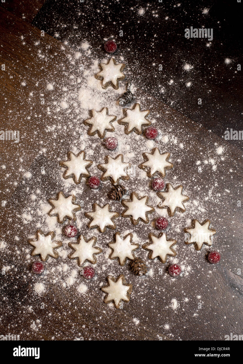 Christmas tree formed of star-shaped cinnamon cookies, red berries and fir cones on wooden table - Stock Image