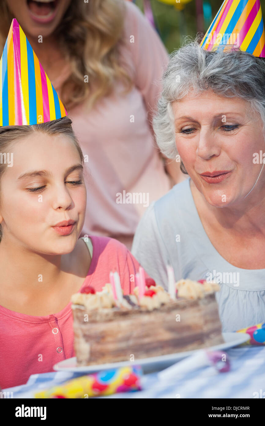 Close up of young girl and her grandmother blowing candles - Stock Image