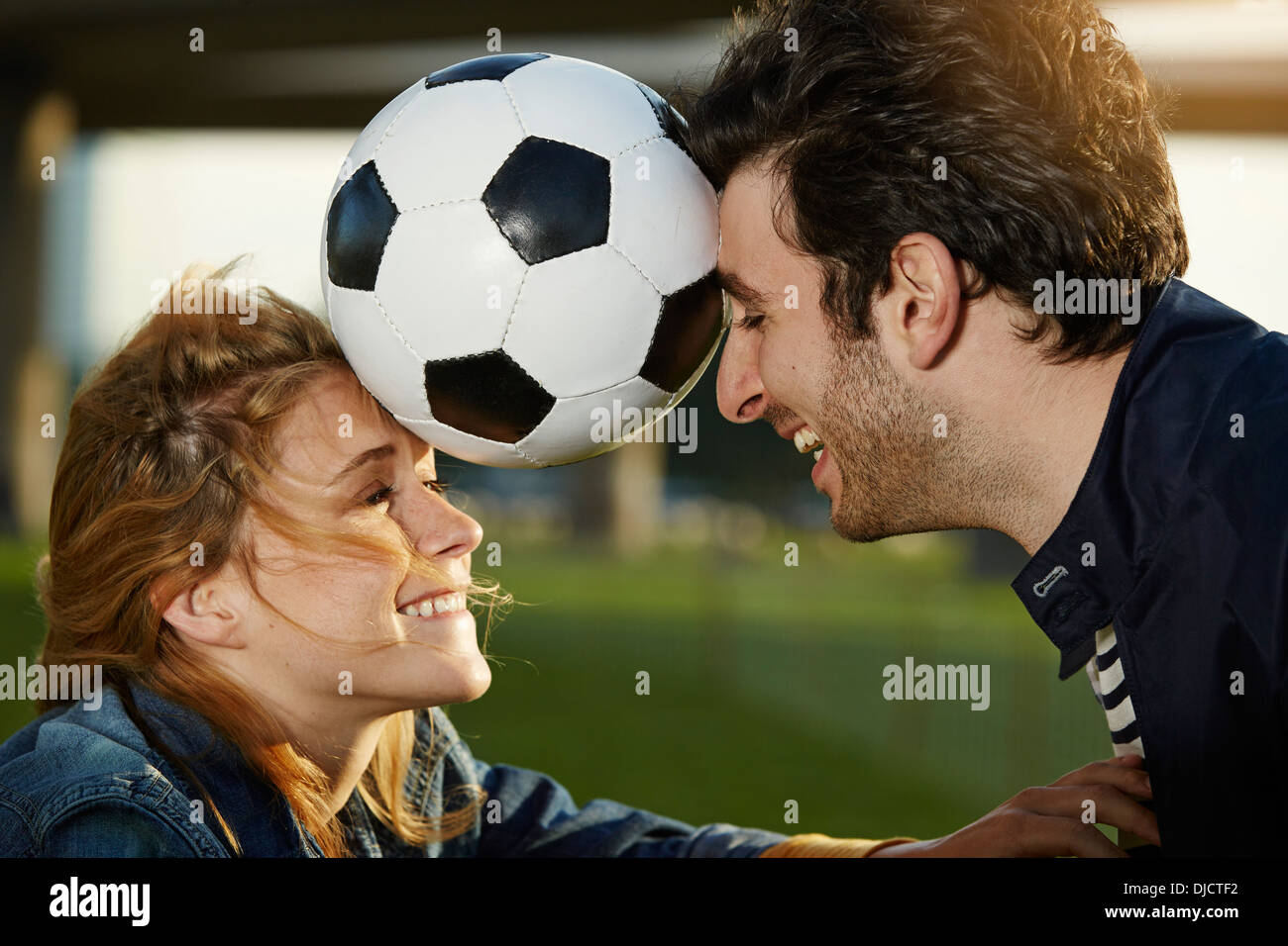Germany, Dusseldorf, Young couple playing football - Stock Image