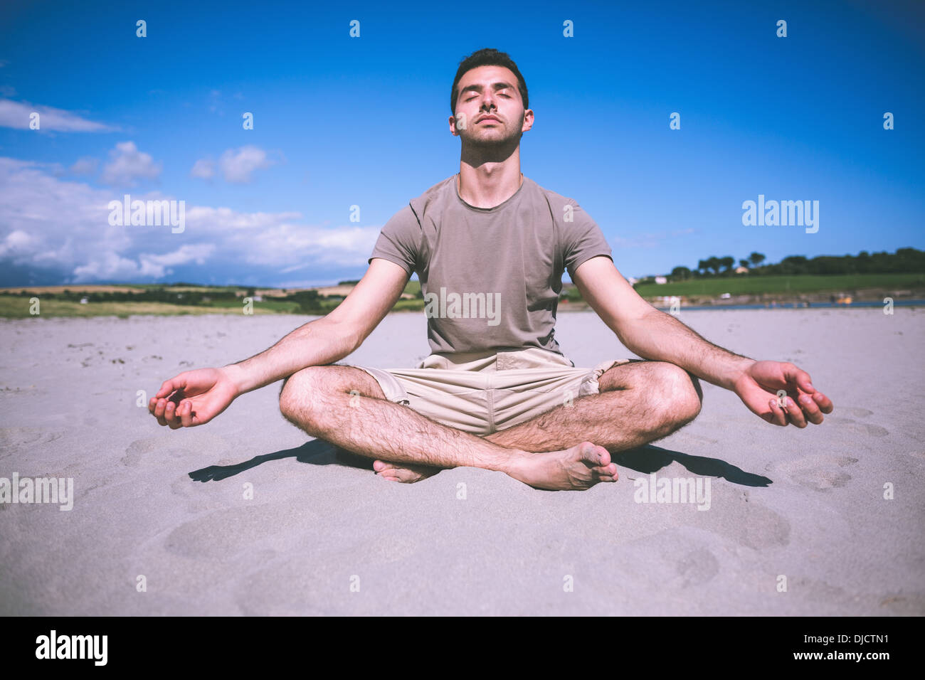 Attractive calm man relaxing with legs crossed - Stock Image