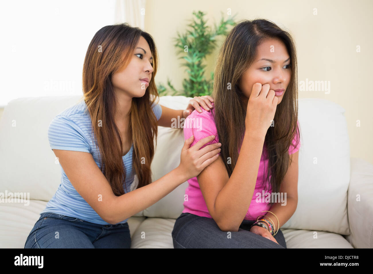 Sad woman sitting on a couch being consoled by her sister - Stock Image