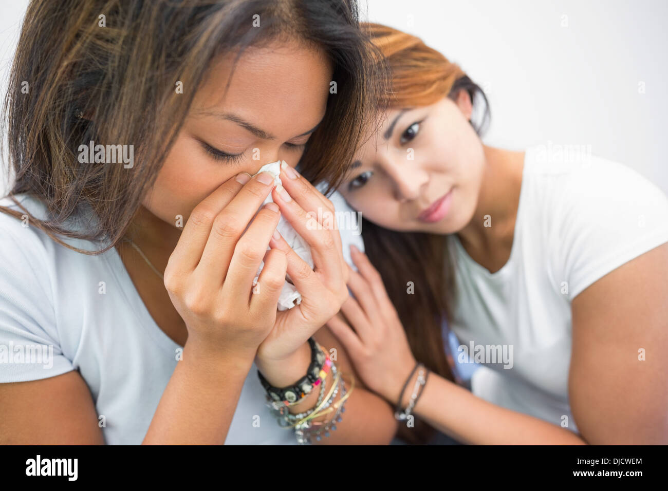 Sad beautiful woman crying while being consoled by her sister - Stock Image