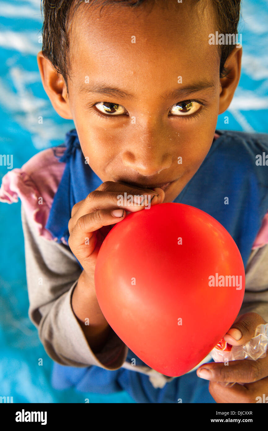 Rosivula, a 6 year old schoolgirl (in her uniform) blowing up a balloon a tourist (a yachtie) had given her. Fulaga, Laus, Fiji - Stock Image