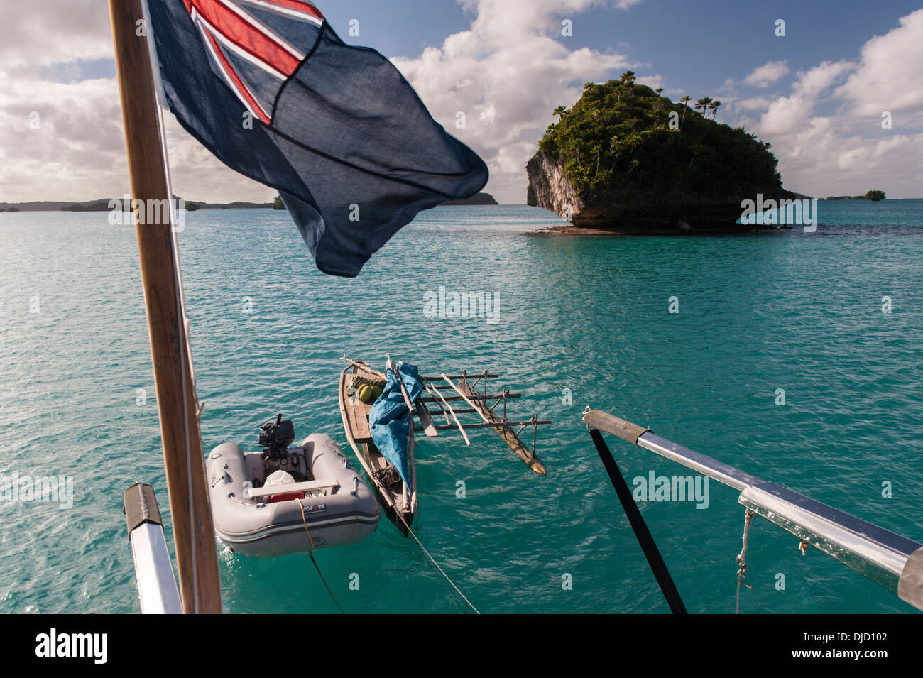 A traditional local sail boat, called a camakau, and a dinghy hanging off the back of a visiting yacht. Fulaga lagoon, Laus Fiji - Stock Image