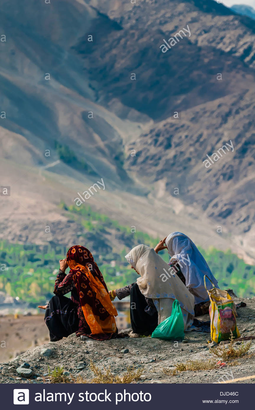 Three Muslim women sit on a rock overlooking the Suru River and the city of Kargil, Ladakh, Jammu and Kashmir State, India. - Stock Image