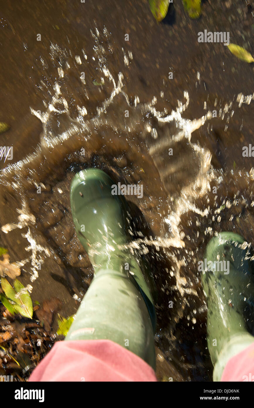 Splashing boots in muddy puddles of water - Stock Image