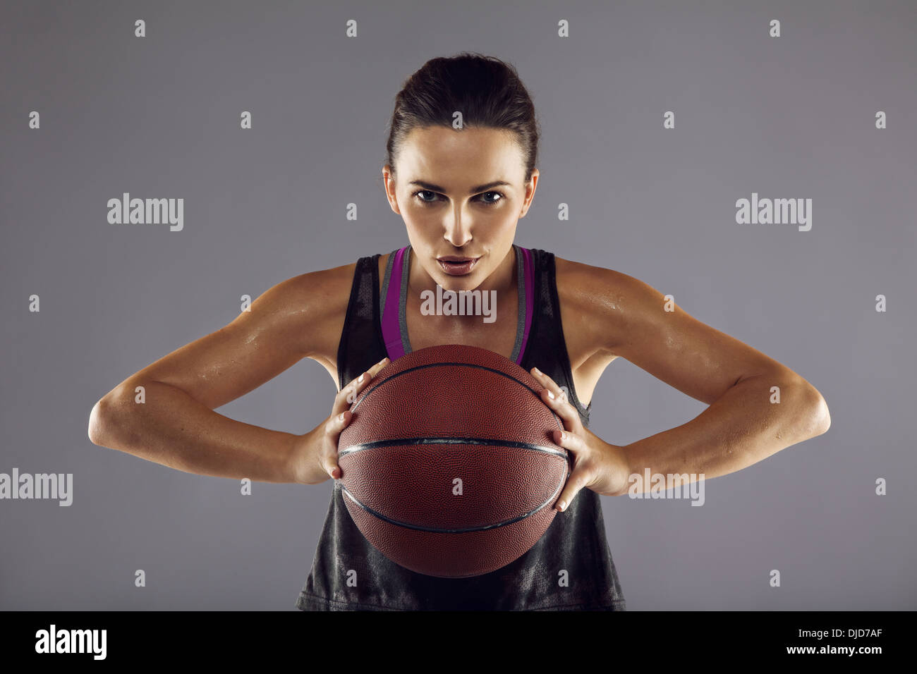 Portrait of happy female basketball player passing the ball. Beautiful young woman in sportswear holding basketball - Stock Image