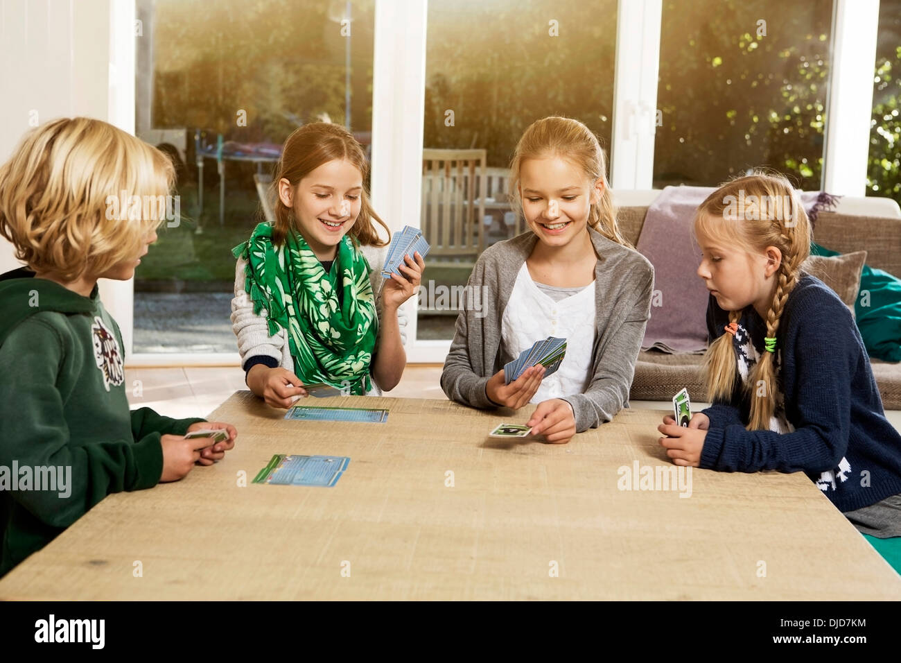 four children playing card game in living room stock photo 62986328 alamy. Black Bedroom Furniture Sets. Home Design Ideas