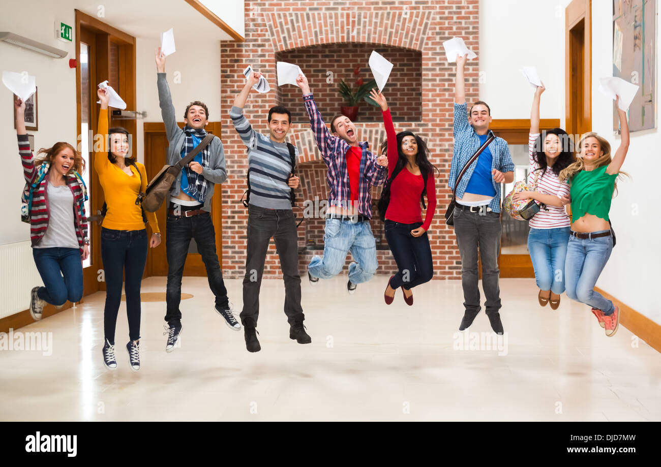Happy students jumping for joy holding exam results in a hallway - Stock Image