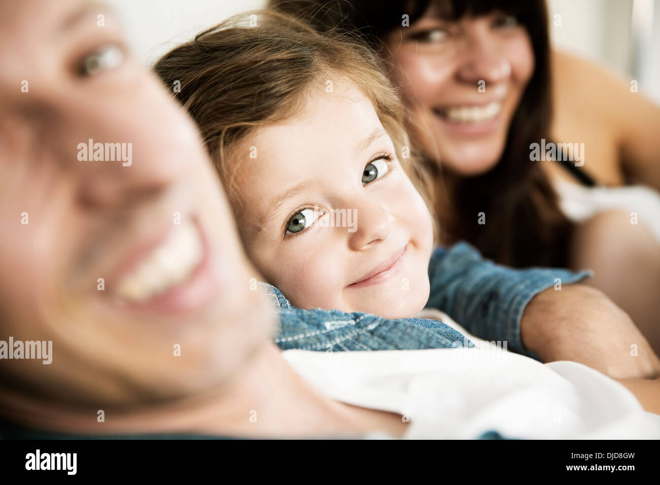 Young parents with little daughter sitting on sofa at home, close-up - Stock Image