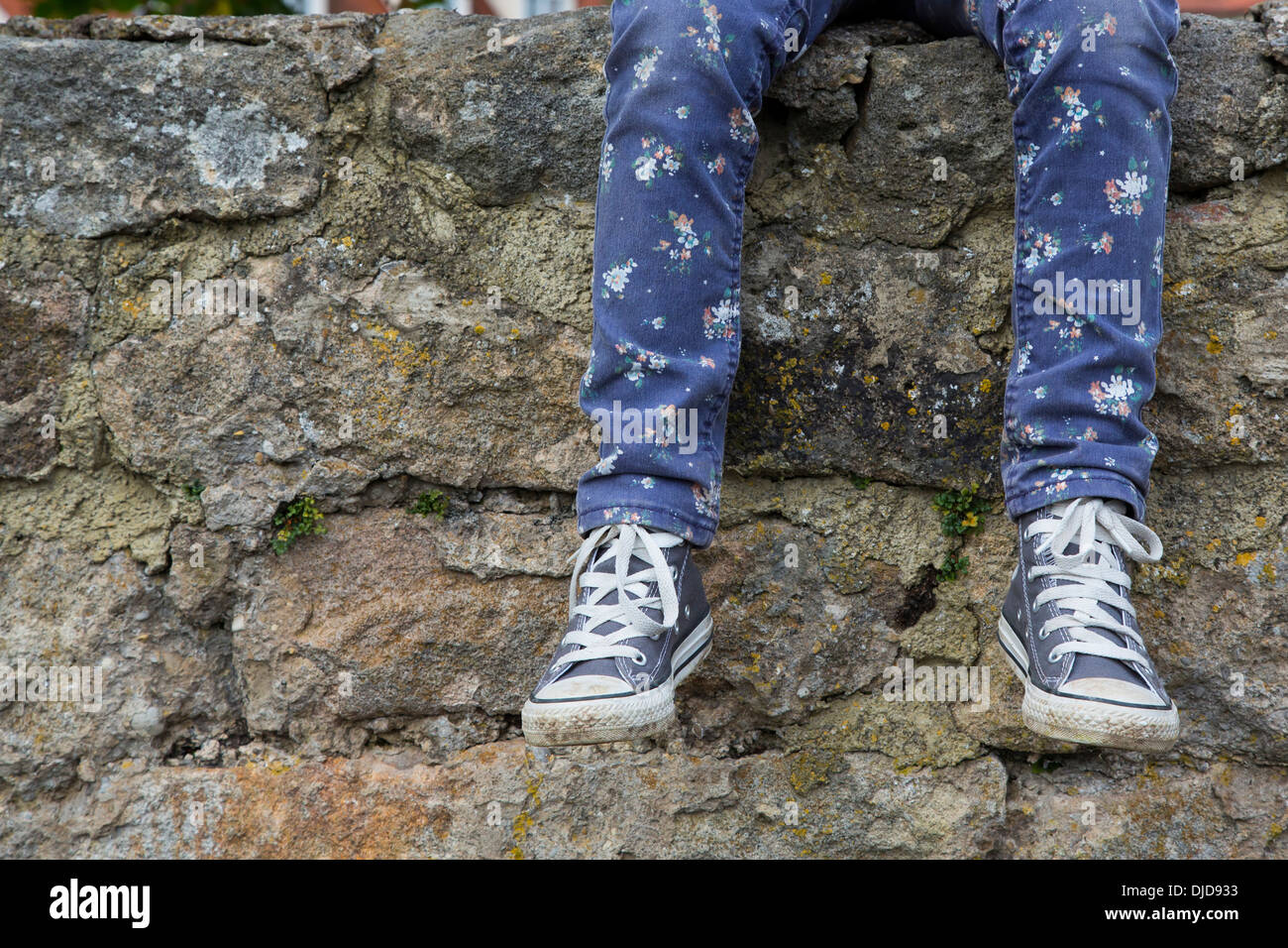 Legs of little girl sitting on a wall - Stock Image