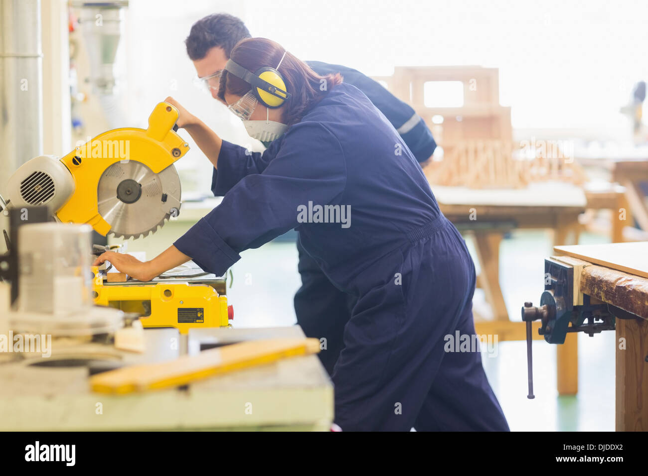 Concentrating trainee sawing piece of wood - Stock Image