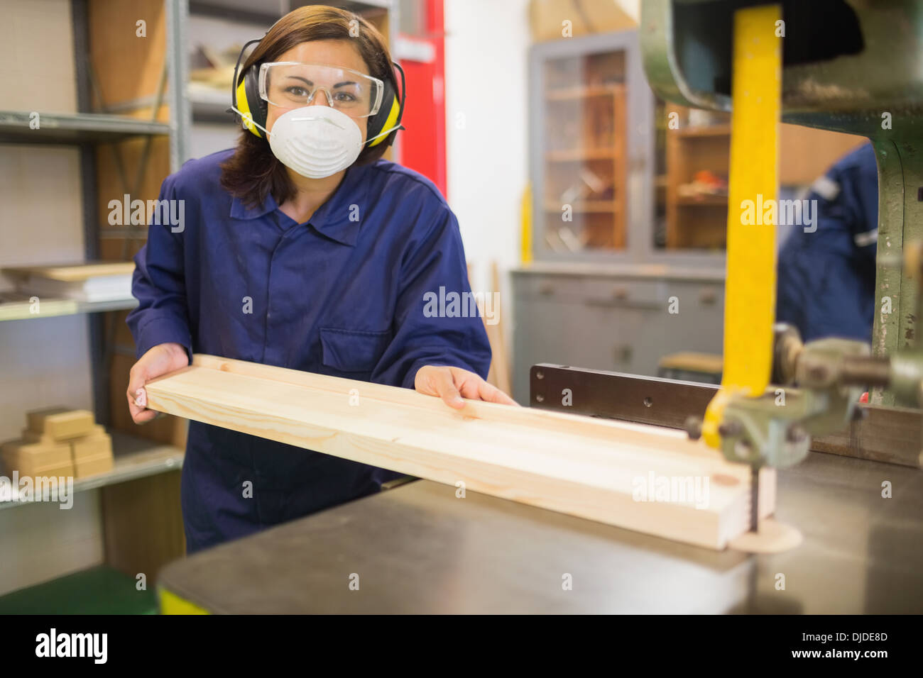 Apprentice wearing safety protection using saw - Stock Image