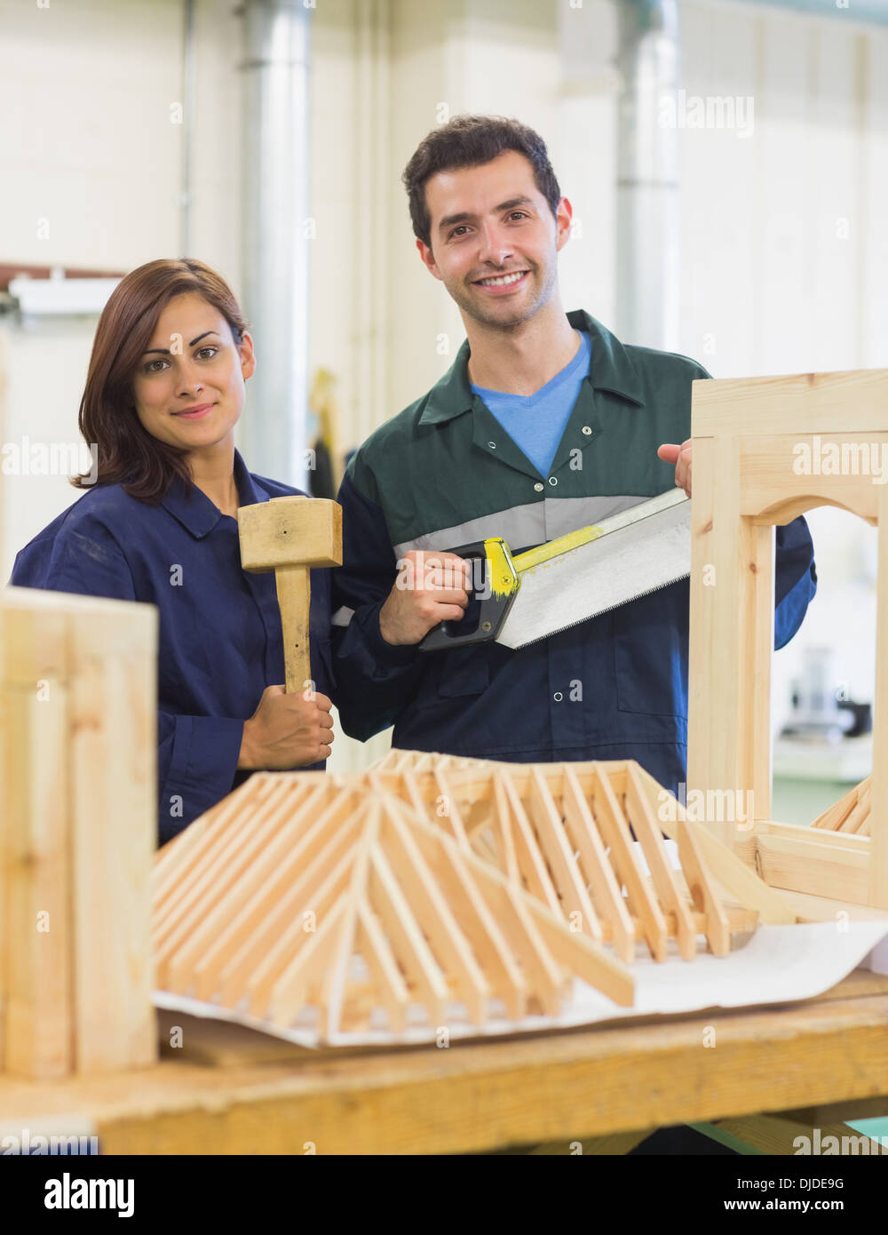 Gleeful trainee and instructor standing behind construction - Stock Image