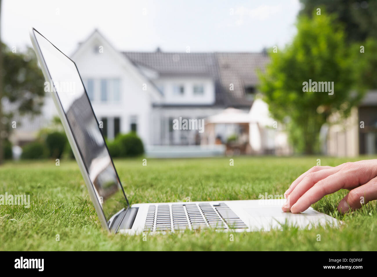 Germany, Cologne, Man using laptop in garden - Stock Image