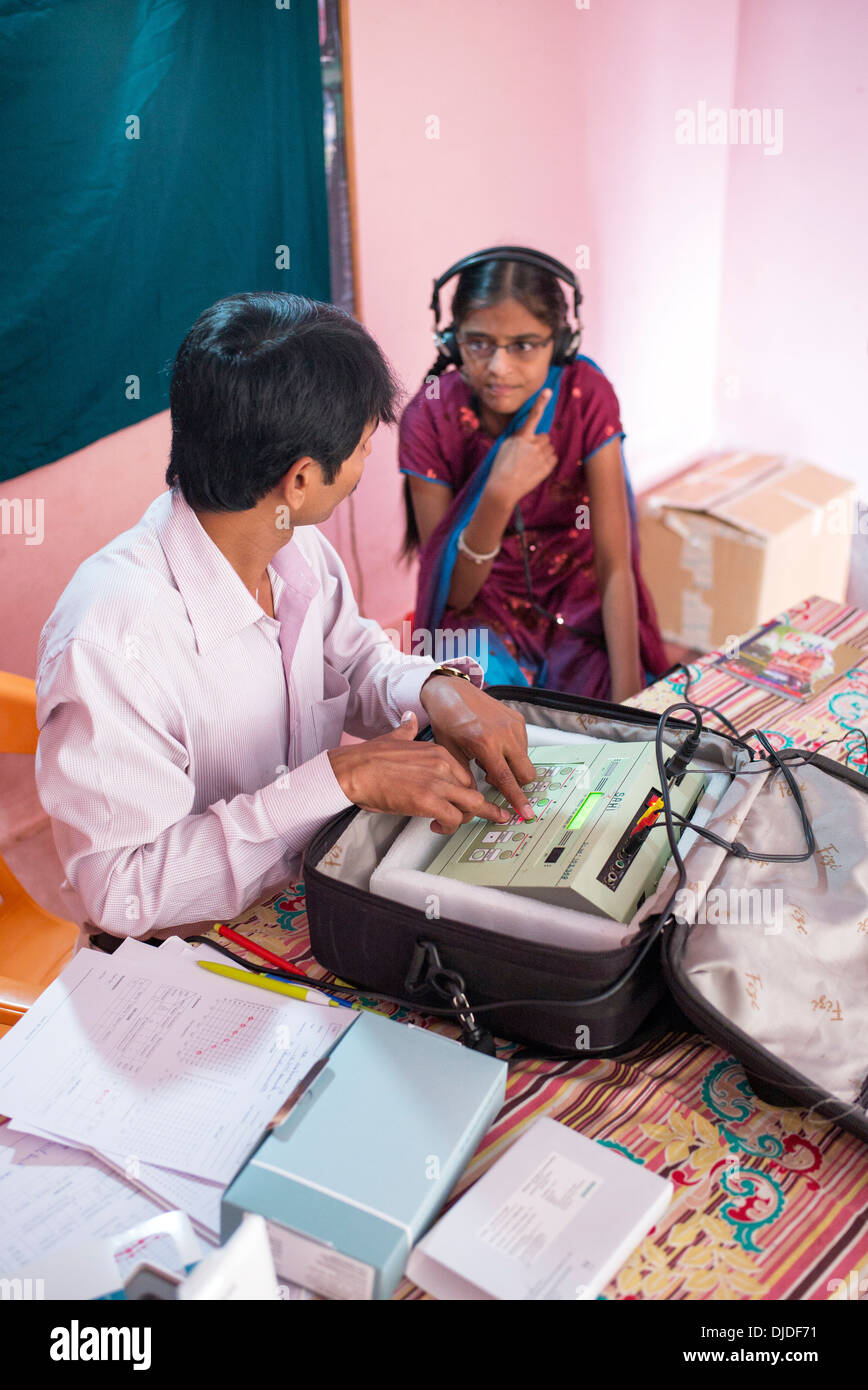 Deaf Indian village girl having a test for a hearing aid at