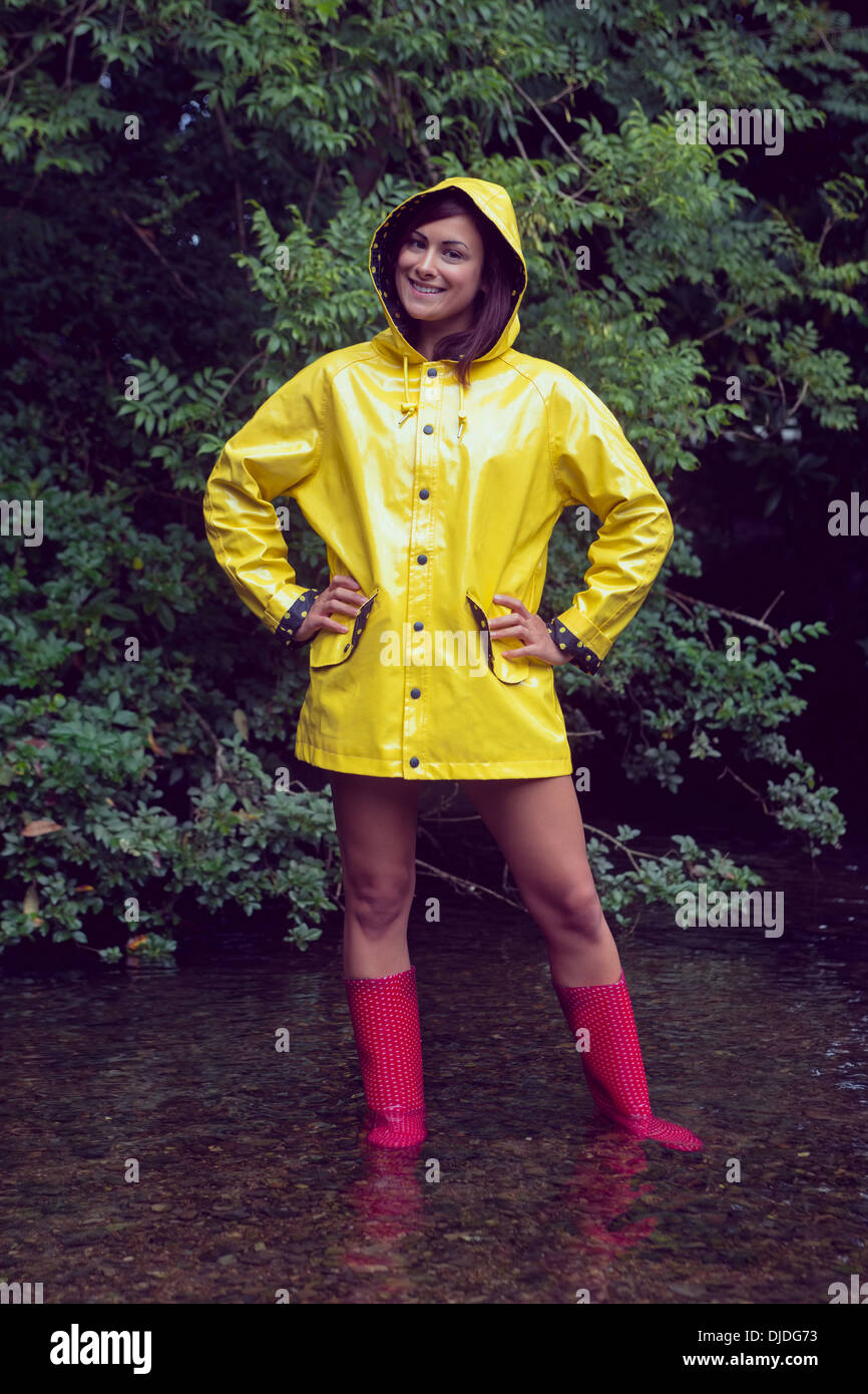 81c96b435 Smiling woman in yellow raincoat and red gumboots against trees ...