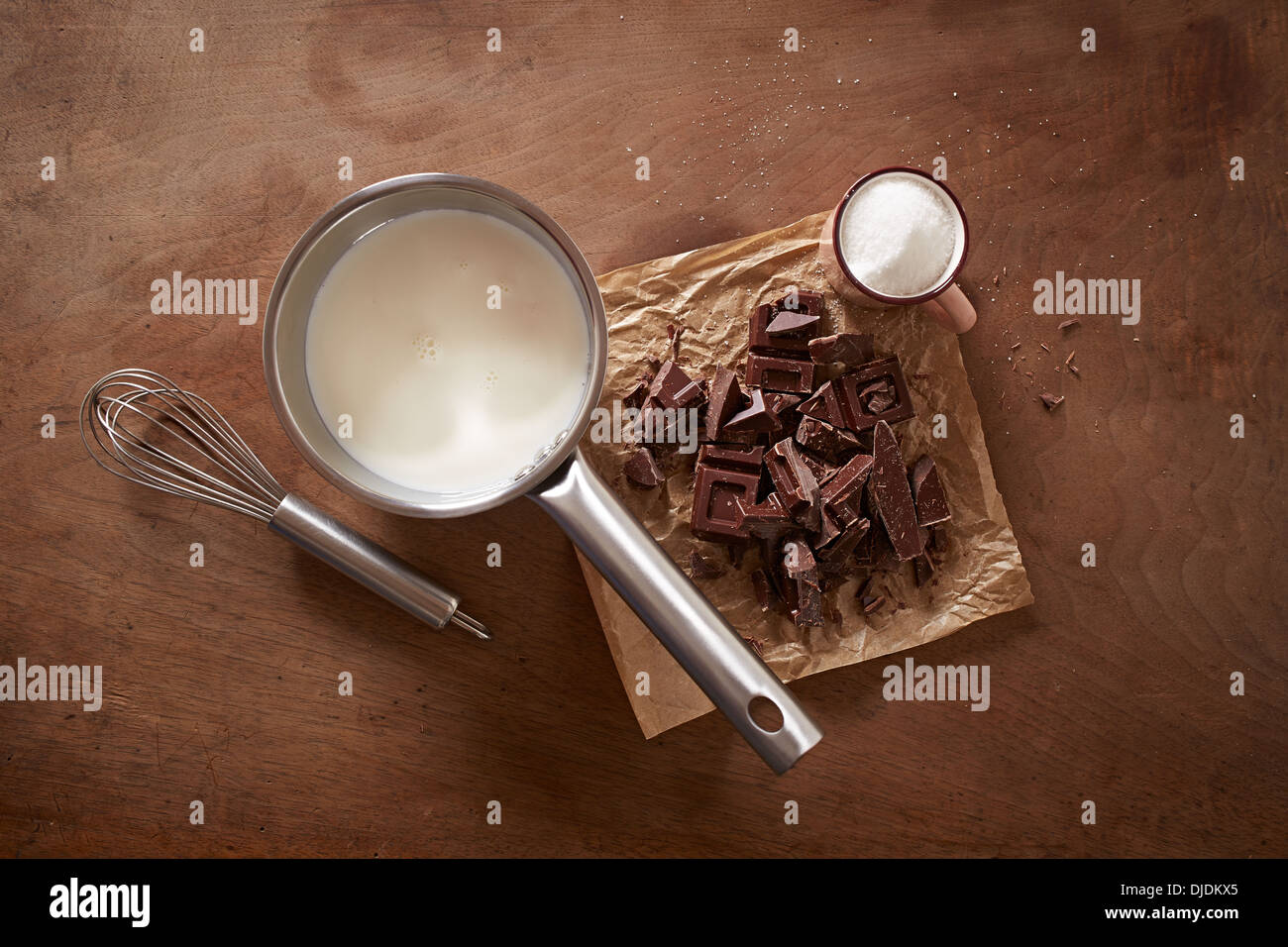 Hot chocolate with milk ingredients on wooden table overlook shot - Stock Image