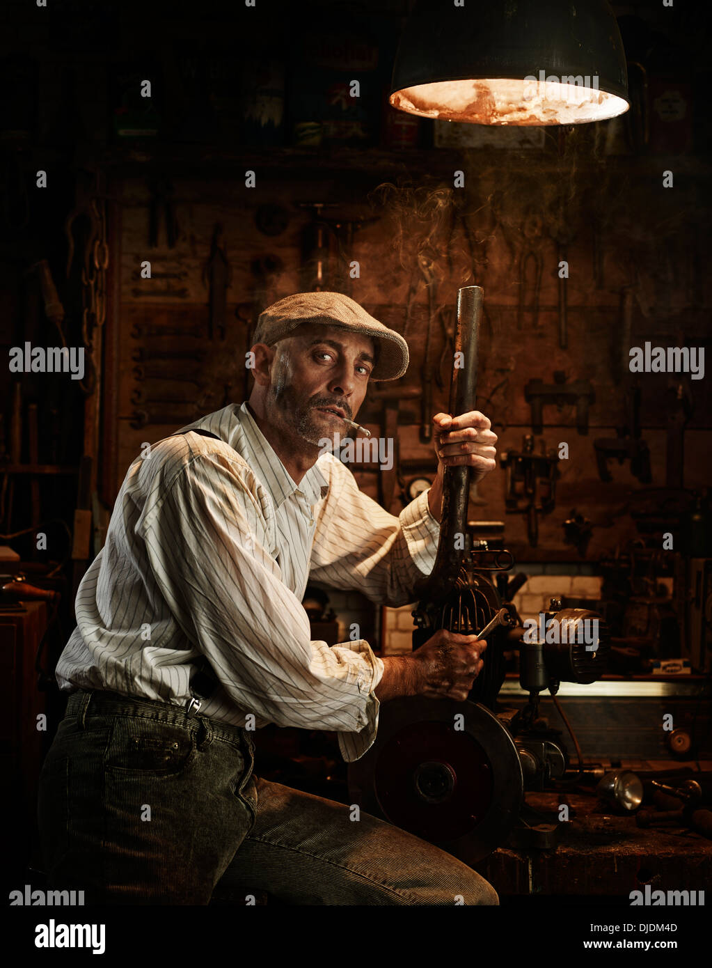 Man with hat and cigarette repairing a motor in a workshop - Stock Image