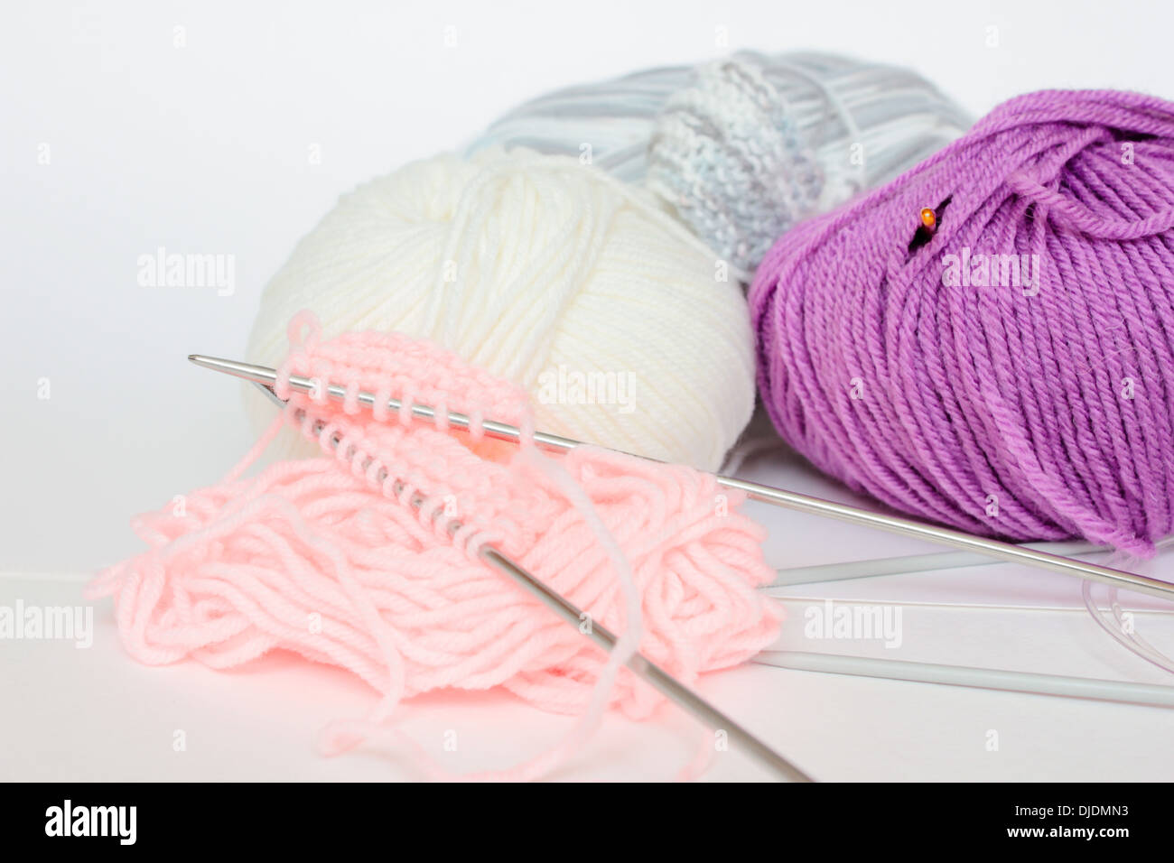 knitting 'knitting needles' yarn skein skeins wool woven purple pink white 'whote background' nobody - Stock Image