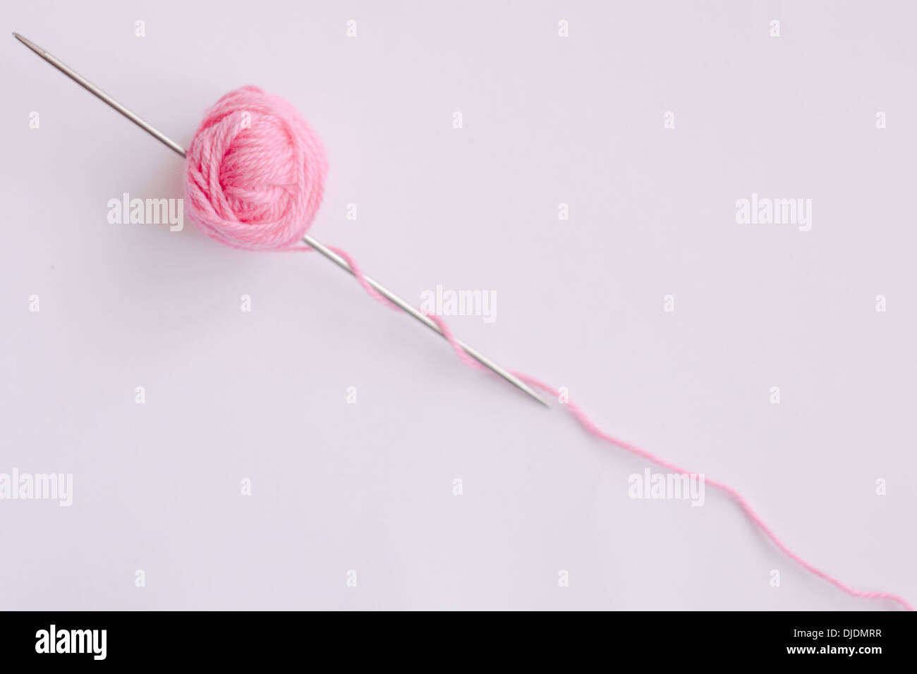 knitting skein pink needle isolated white diagonal nobody - Stock Image