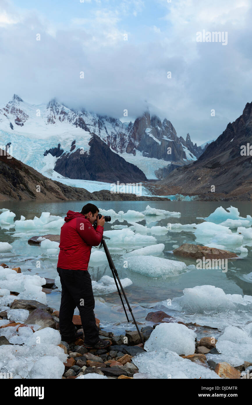 Tourist photographing Icy glacier waters of Lago Torre and Cerro Torre mountains in the background.Patagonia.Argentina - Stock Image