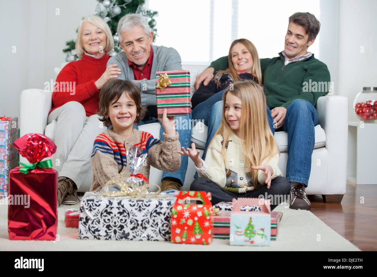 Boy Holding Christmas Gift With Family In House - Stock Image