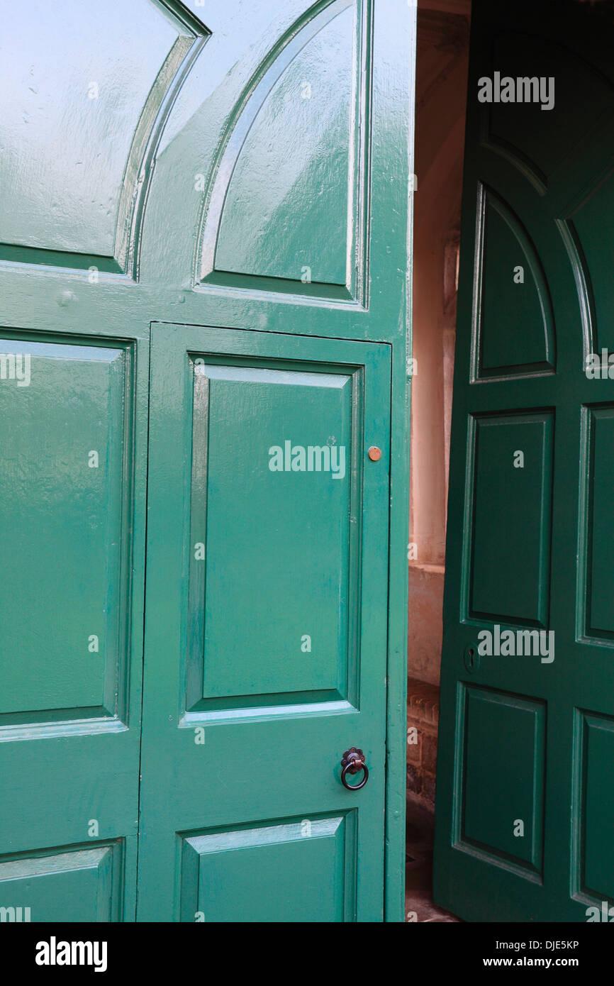 Green door ajar. Entrance to Wymondham Abbey. - Stock Image