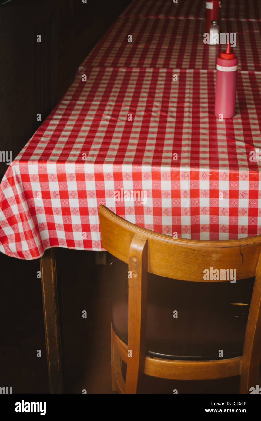 Iconic red and white checkered table cloth covering the table of a BBQ joint along route 281 in the heart of Texas Hill Country. - Stock Image