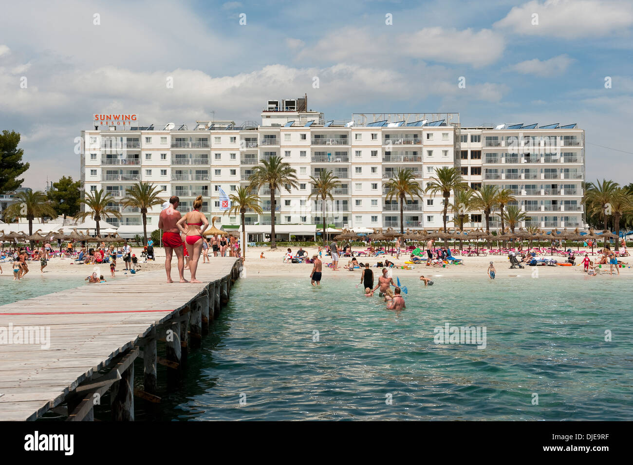 Holidaymakers sunbathing on the beach in front of the Sunwing Resort hotel, Mallorca - Stock Image