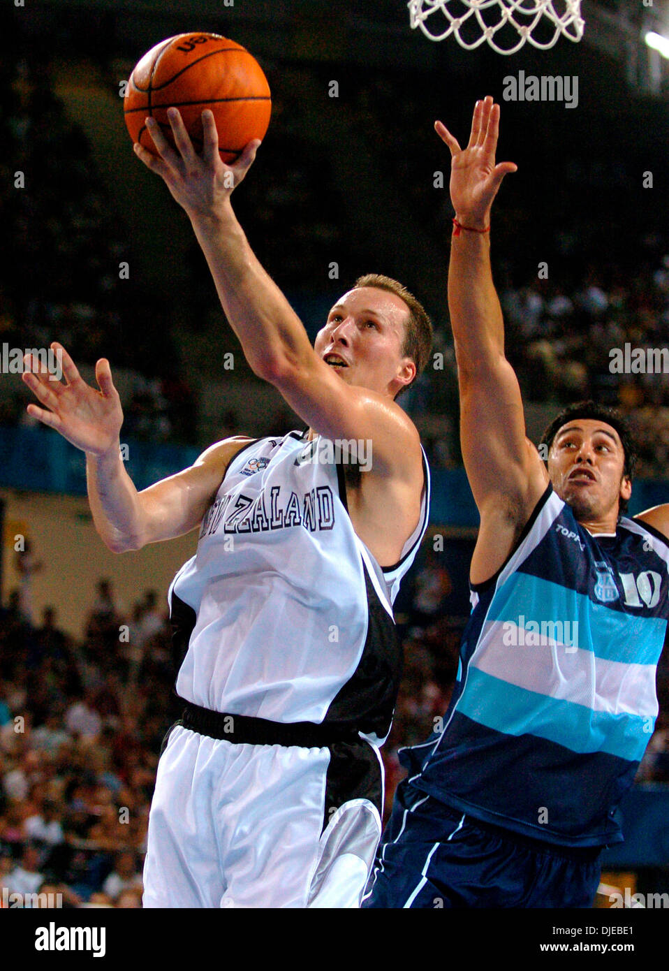 Aug 21, 2004; Athens, Greece; New Zealand Olympic basketball team member Phillip Jones goes past Argentina's Hugo Ariel Sconochini on his way to the hoop during preliminary round basketball play. - Stock Image