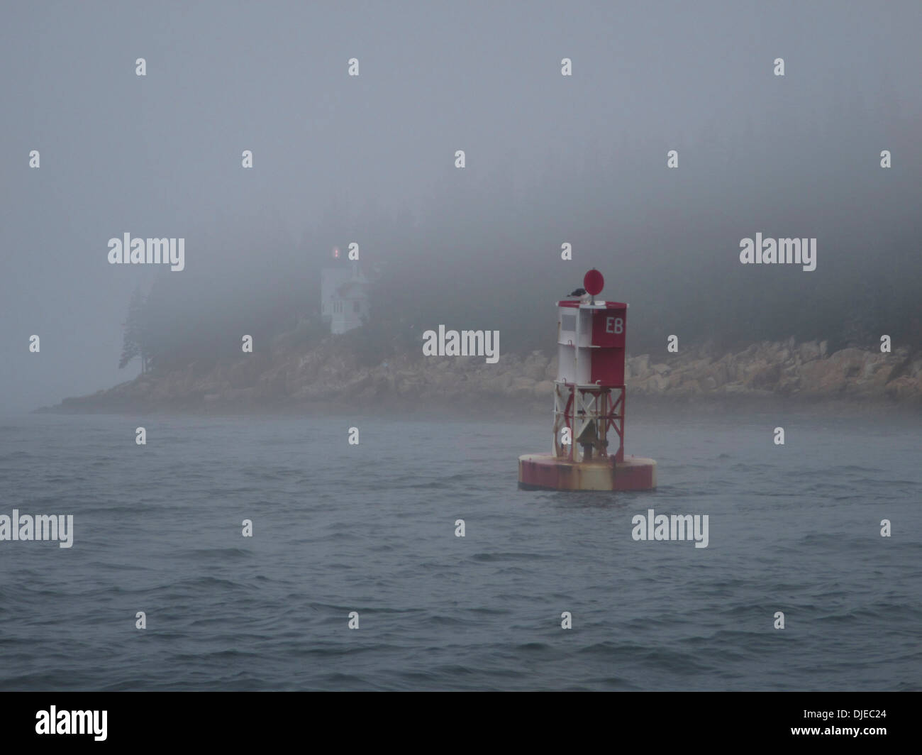 A red and white buoy and the Bass Harbor lighthouse in the fog along the coast of Maine USA - Stock Image