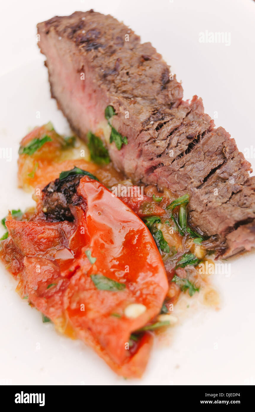 Cooked slice of meat with spicy salsa on white plate. Stock Photo