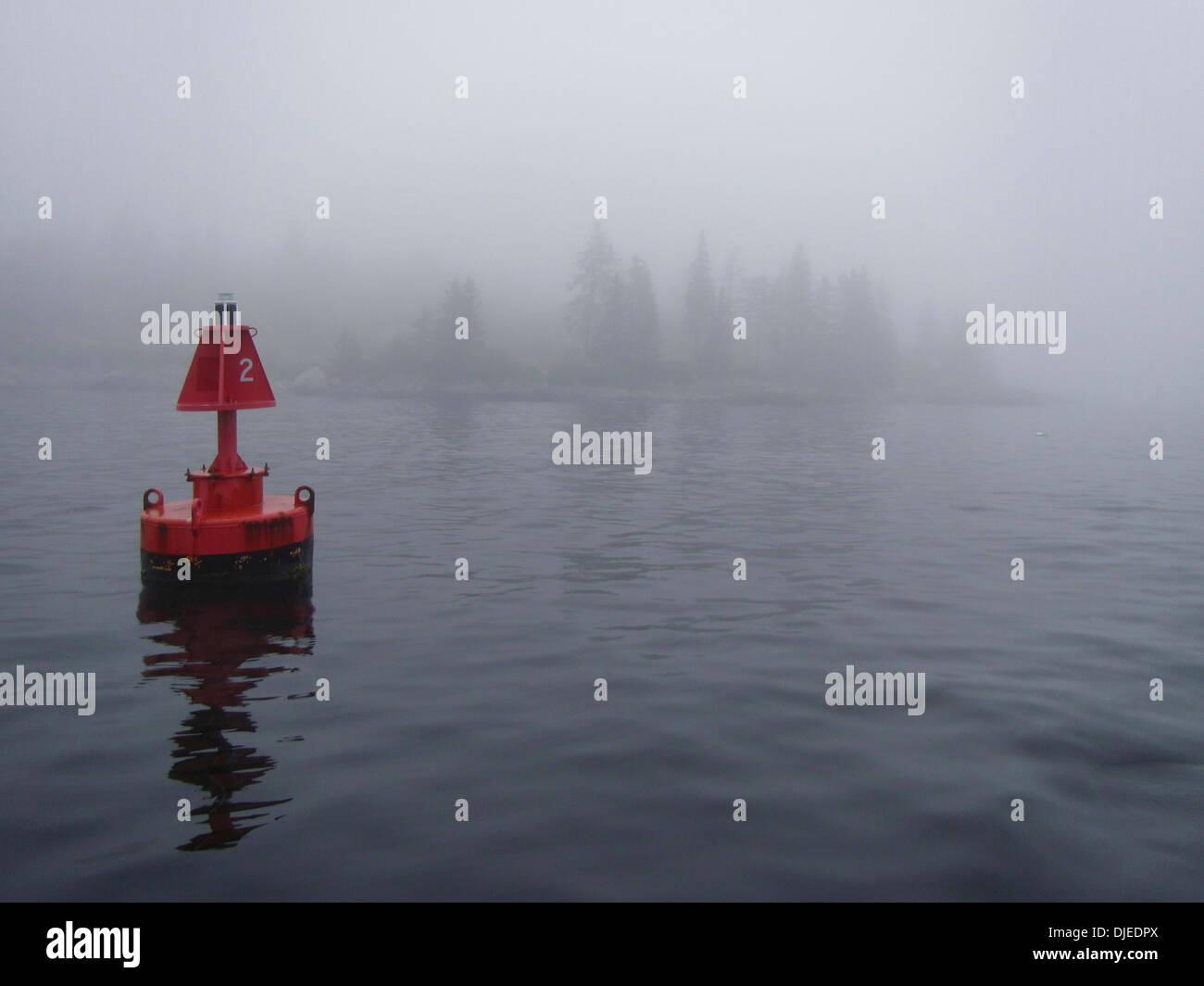 A fog bound island and navigational buoy along the coast of Maine. - Stock Image