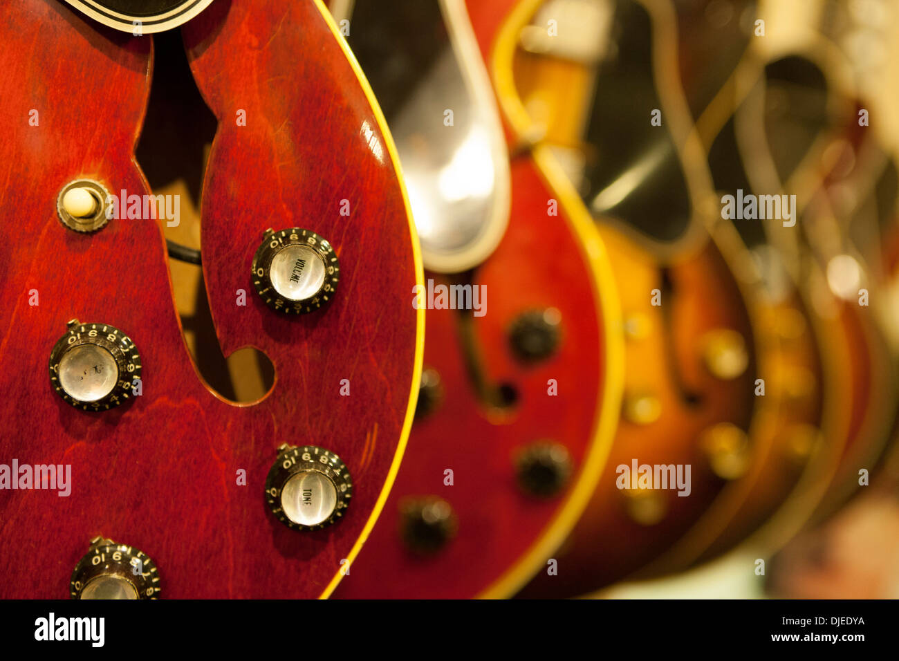 A close up of a red electric guitar and its various sound controls such as volume. It appears to be used and for sale in a store - Stock Image
