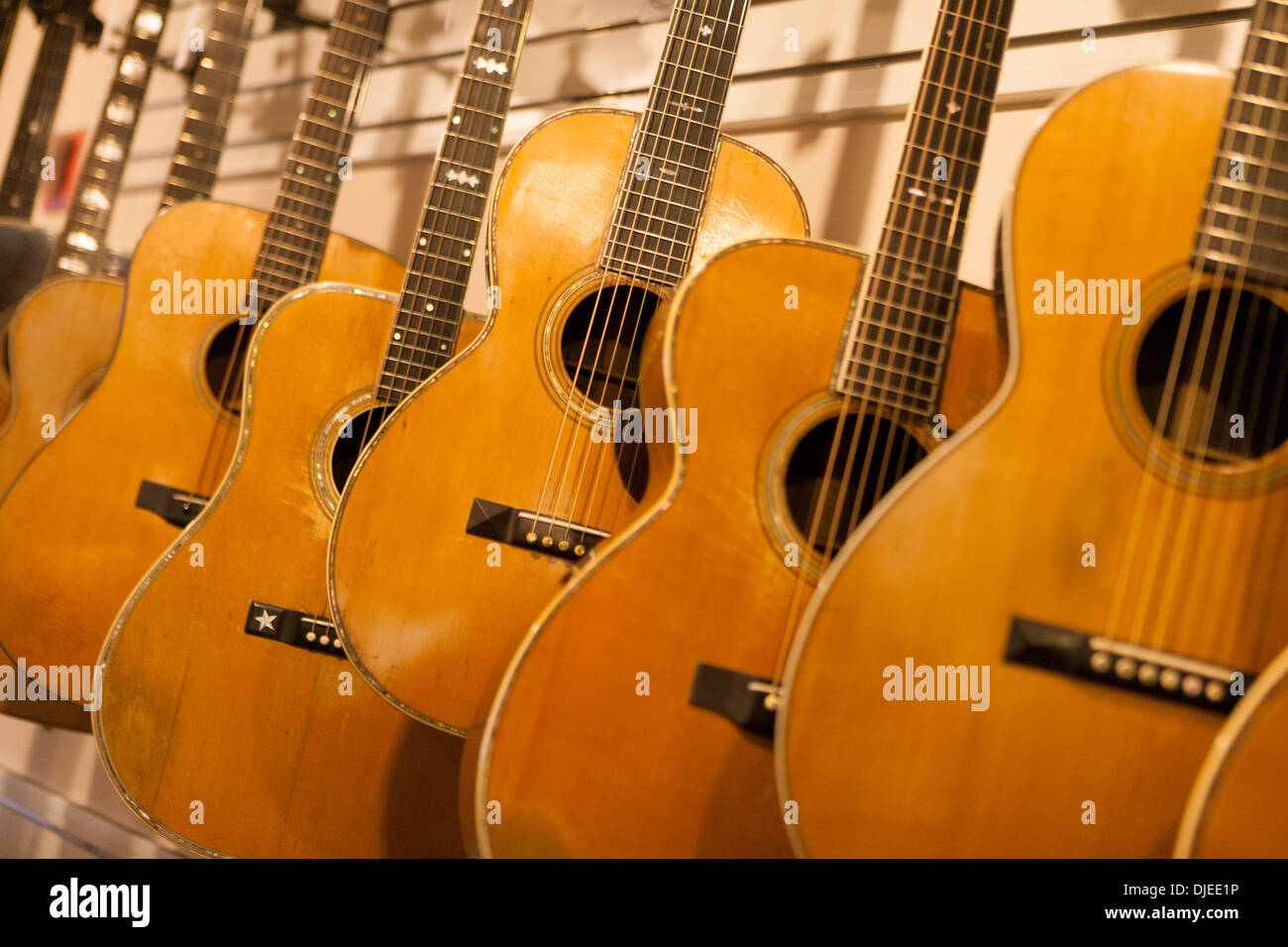 wooden acoustic guitars for sale in a music shop - Stock Image