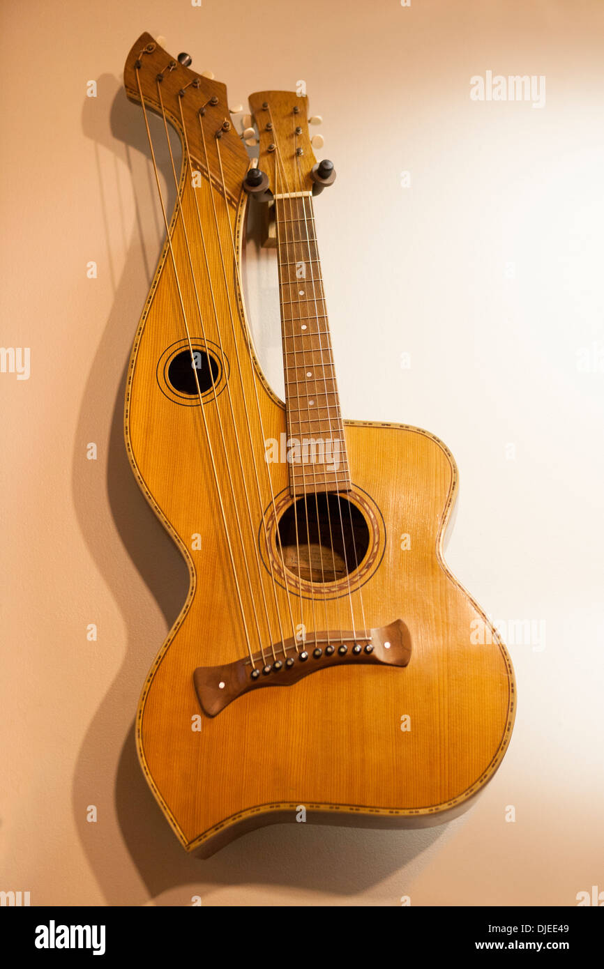 An old harp guitar, so called for its unfretted strings next to the fretted ones. The harp strings have their own neck. - Stock Image