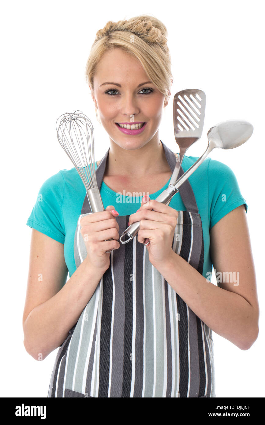 Model Released. Attractive Young Woman Holding Stainless Steel Kitchen Utensils - Stock Image