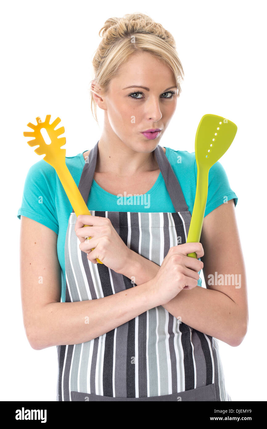 Model Released. Attractive Young Woman Holding Kitchen Utensils - Stock Image