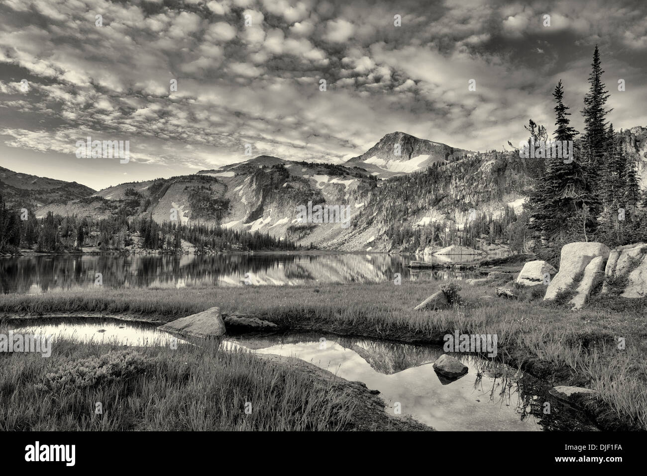 Evening light and reflection in small stream and Mirror Lake with Eagle Cap Mountain. Eagle Cap Wilderness, Oregon - Stock Image