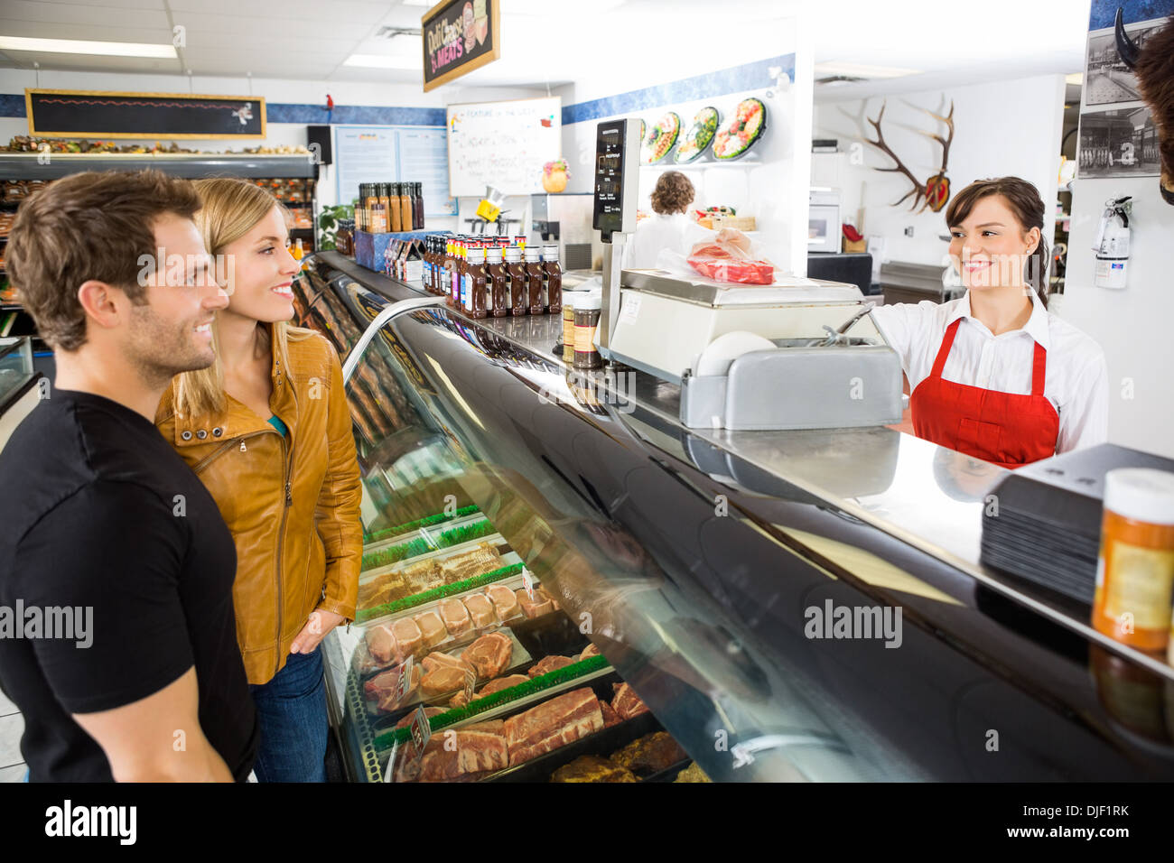 Saleswoman Attending Customers At Butcher's Shop - Stock Image
