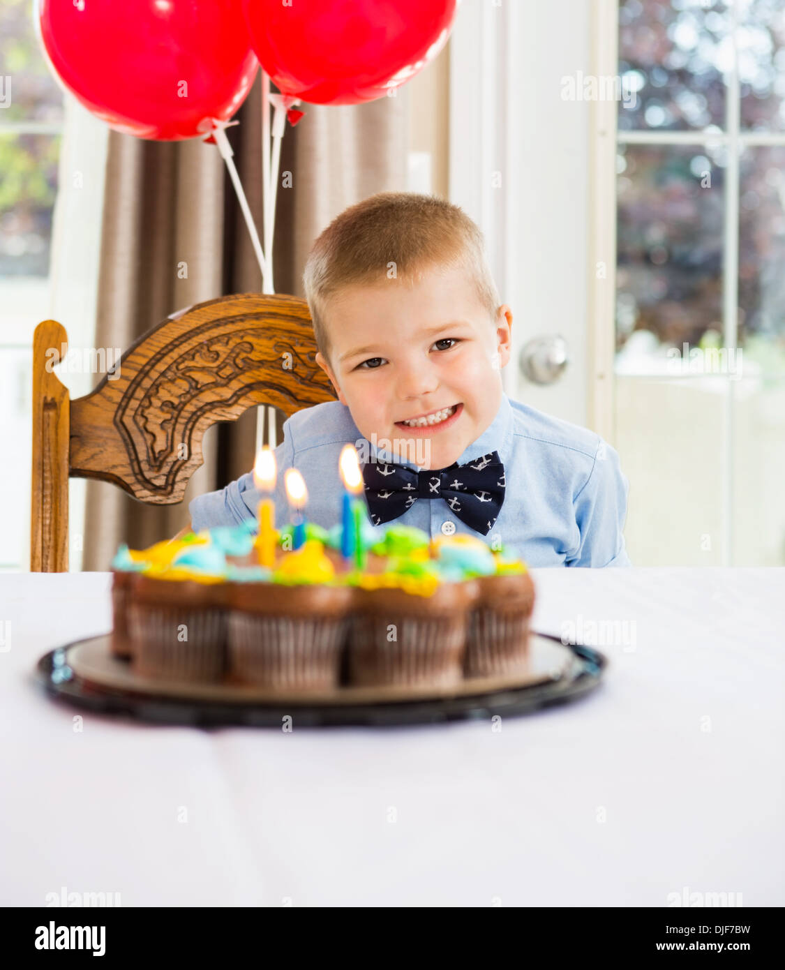 Happy Boy Sitting In Front Of Birthday Cake - Stock Image