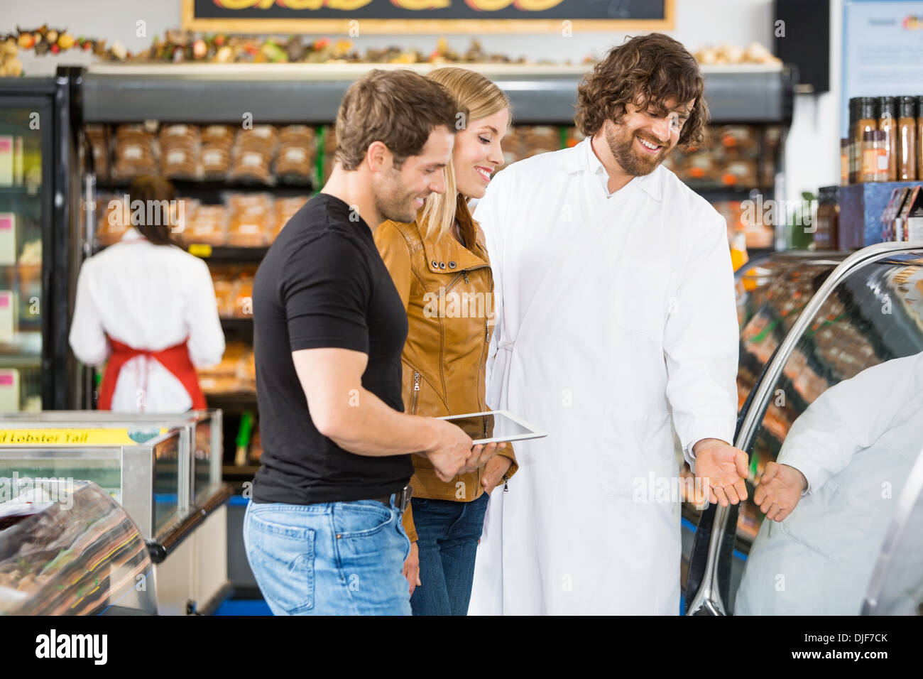 Salesman Assisting Couple In Buying Meat - Stock Image