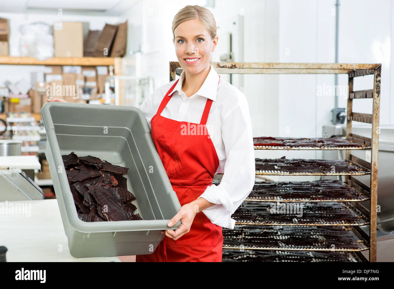 Worker Showing Beef Jerky In Basket At Shop - Stock Image