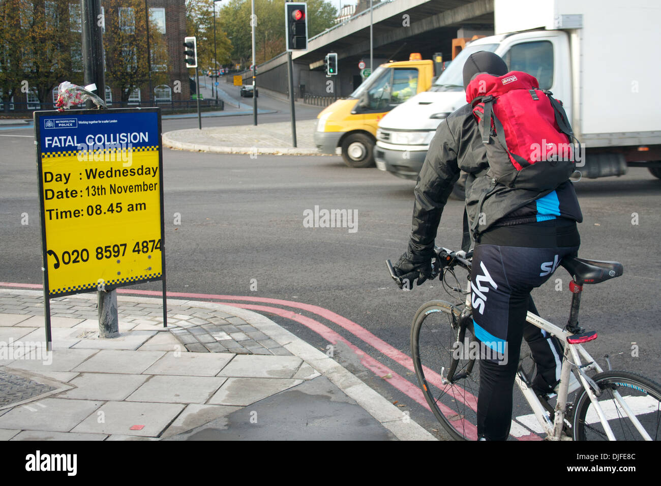 Cyclist, police sign and traffic at Bow flyover, London - Stock Image